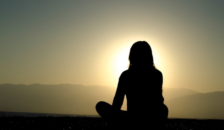 female meditating with the sunrise in the distance